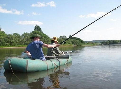 Рыболов ловит с лодки на реке с помощью удочки