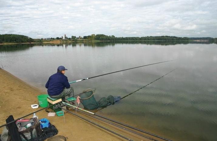 рыболов на бреге сидит на штекер глядит