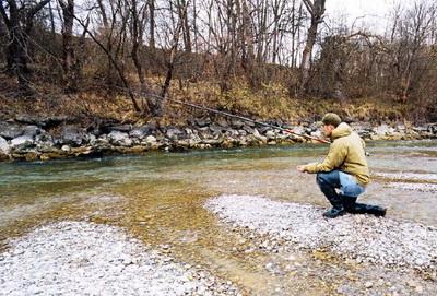 Рыболов ловит форель на реке