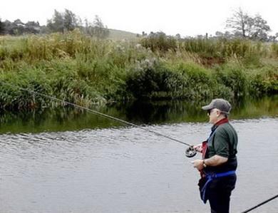 Рыболов на берегу реки с удочкой
