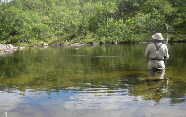Рыболов ловит удочкой в проводку на реке