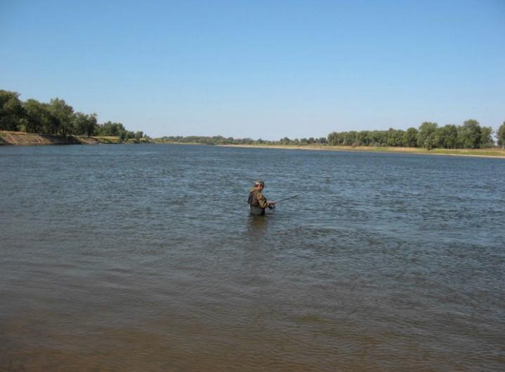 Рыболов находится в воде в реке летом